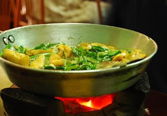A pan of sautéed fish, turmeric and dill