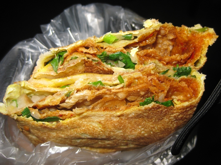 Closeup of layers of filling in a jianbing