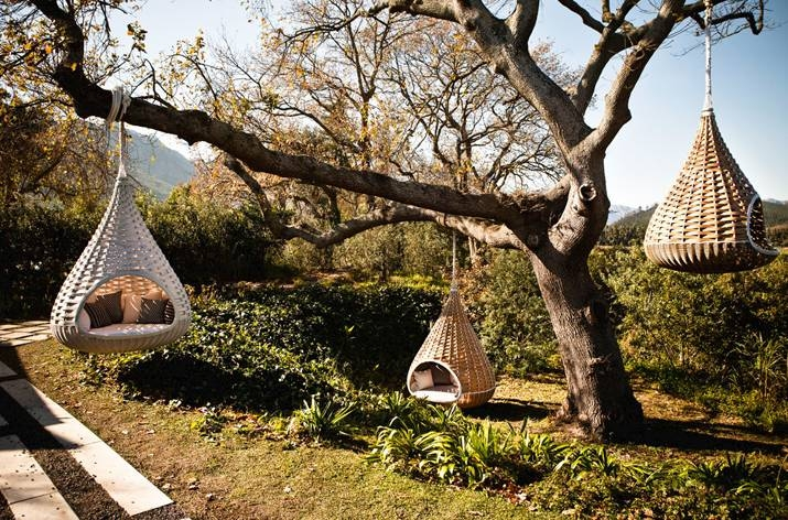 Lounge chair/shelter resembling a large bird's nest shown hung from the trees.