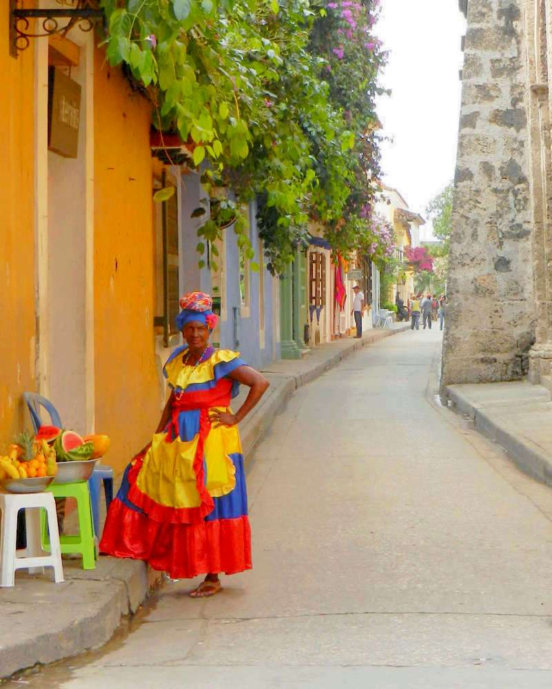 A lady selling fruits at a street corner of old town in Cartagena
