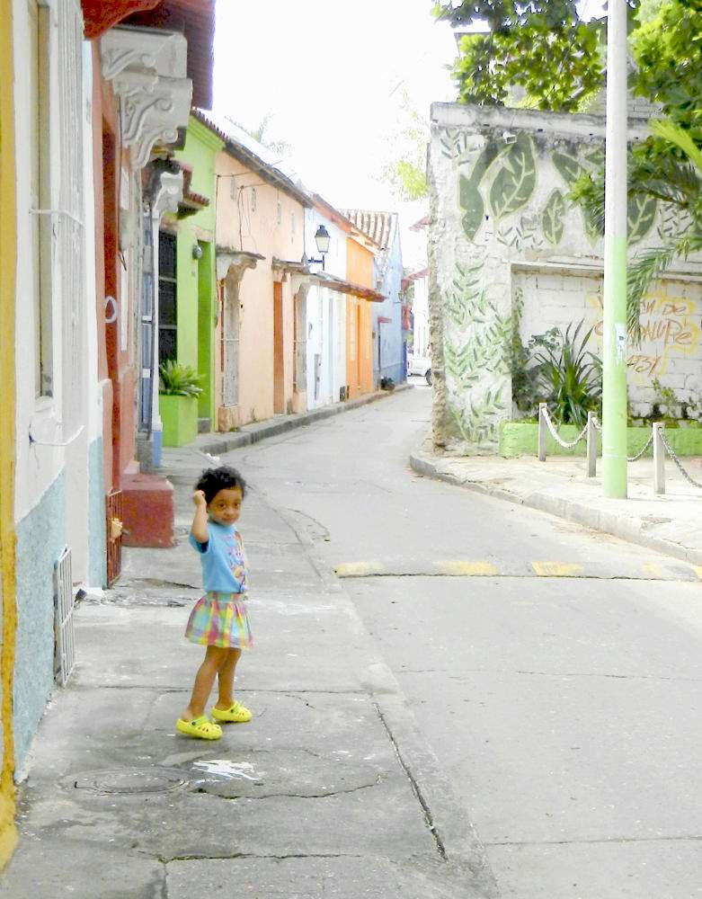 Child in a street of colorful houses in Getsemani, Cartagena