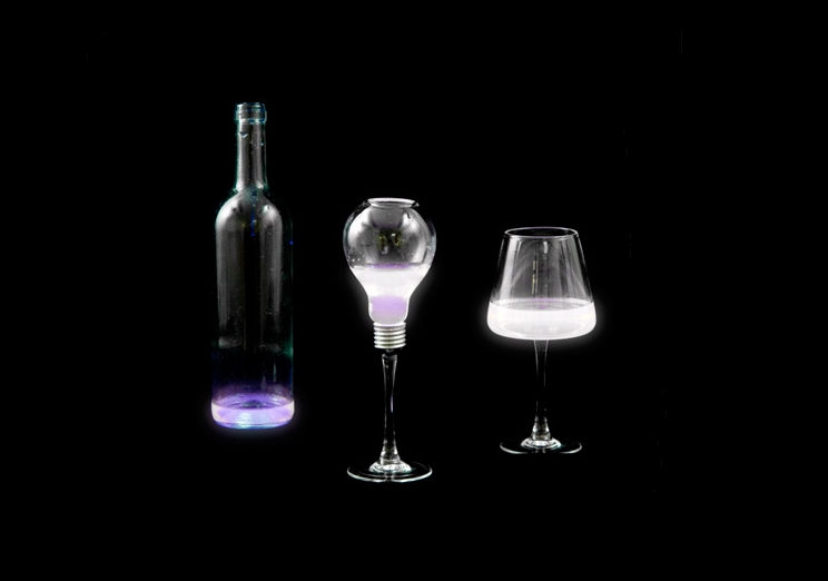 A bottle and 2 glasses of chemoluminescent reagents glowing in the dark