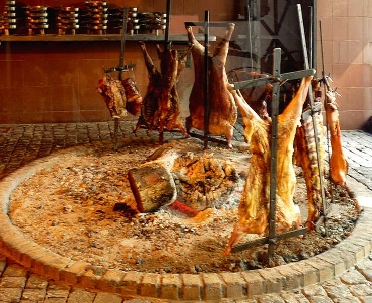A traditional open fire pit with pig and goat at La Chacra.