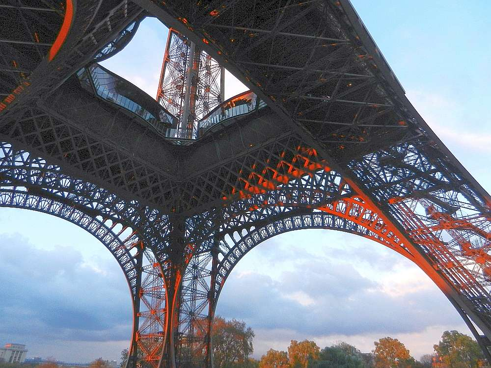 The base of the Eiffel Tower glowing red in the sunset