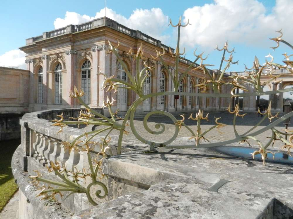 The Grand Trianon viewed through gilded wrought iron fence.