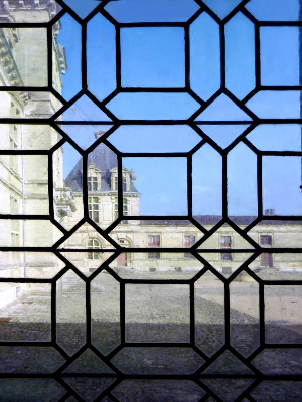 View of the Chateau's courtyard through its leaded glass window.