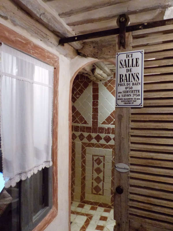 Our bathroom features a barn door with vintage sign on charges for use of a public bathroom