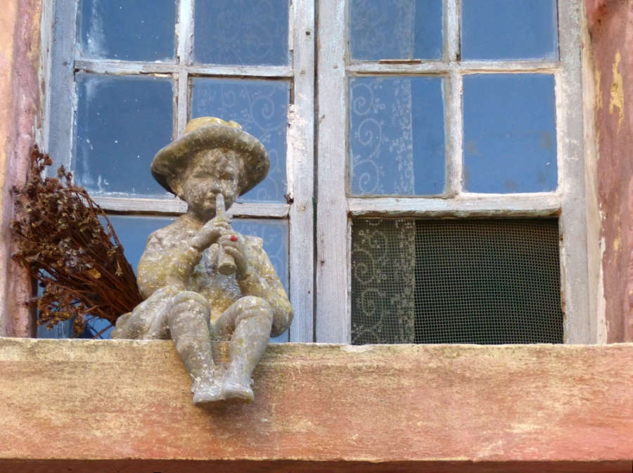 Vignette of small wood carving of a boy playing flute next to a sprig of dried flowers on a window sill