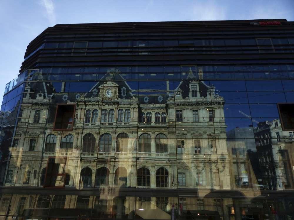 Reflection of Palais de la Bourse in building glass wall