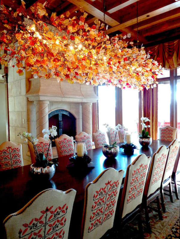 Colorful chandelier of resin piece over dining table.