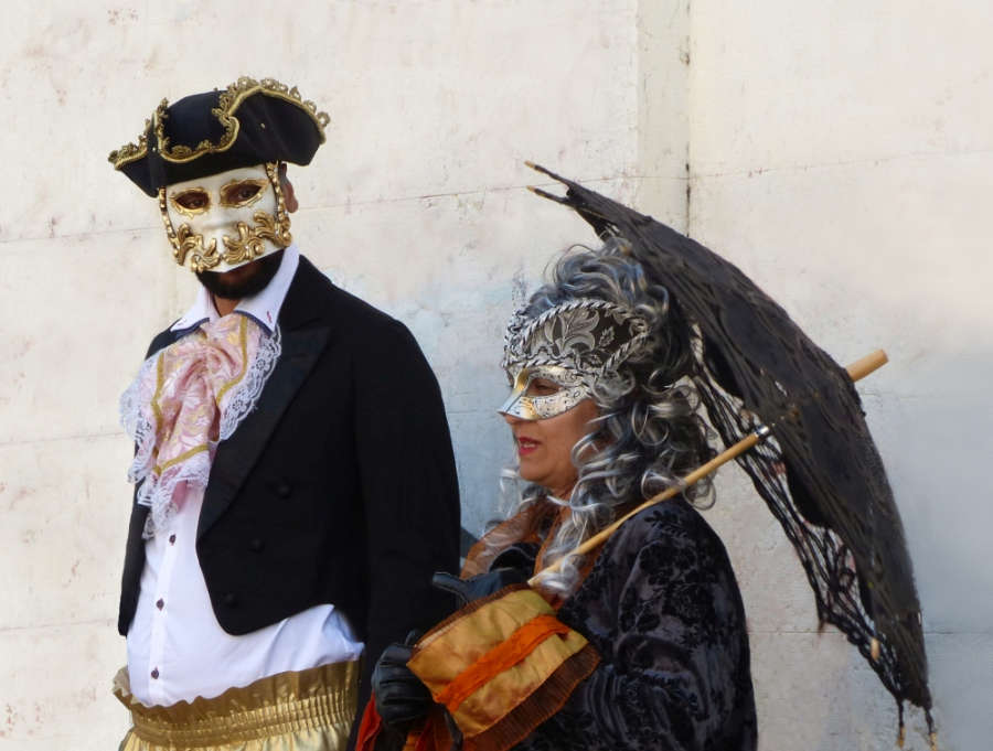 A couple in masks and period costume.