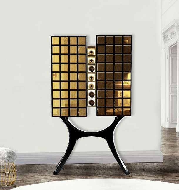 A bar cabinet with 2 gold mirrored towers on a curved black lacquered legs
