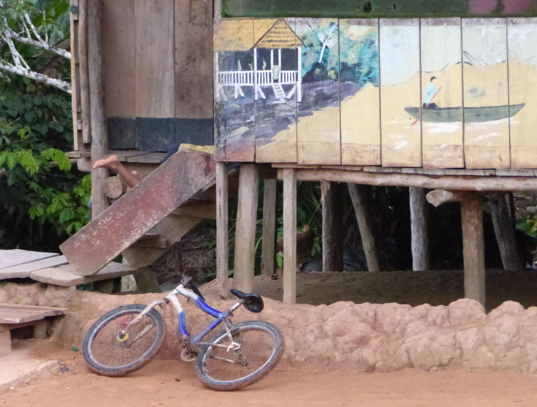 Child playing on steps of home in Puerto Prado Village