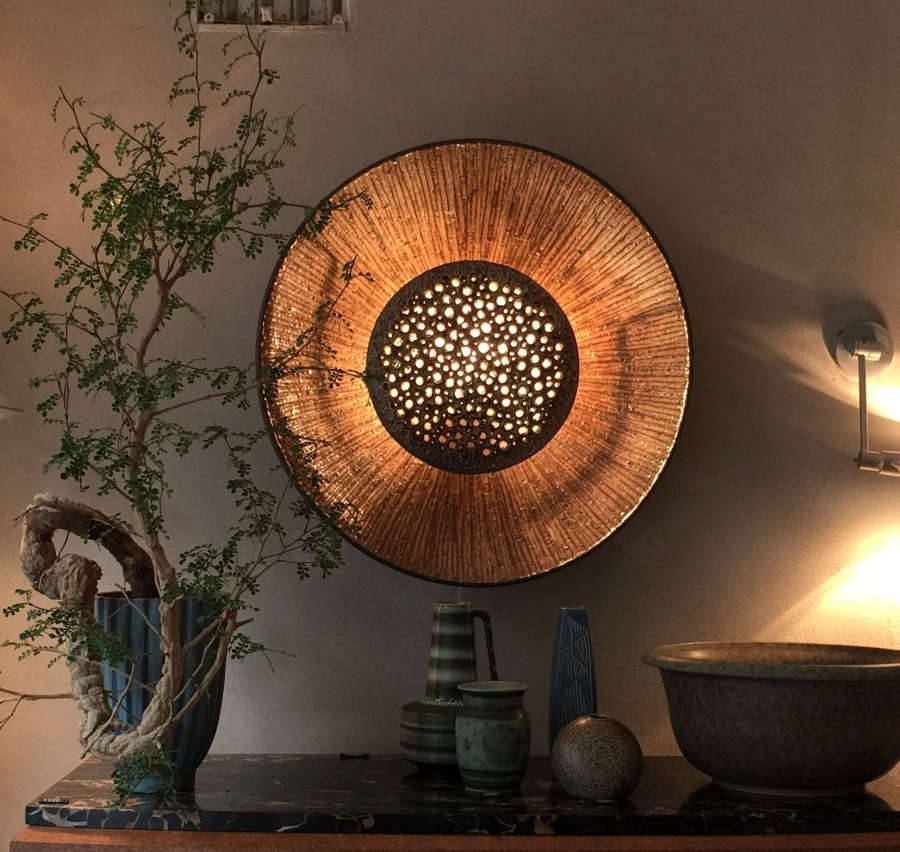 Ceramic wall sconce that resembles a sunflower.