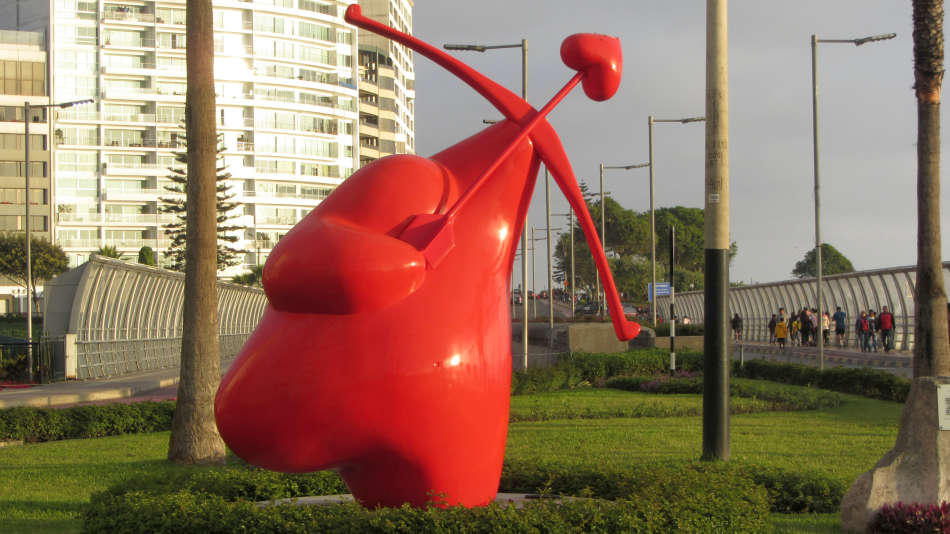 Red heart shaped sculpture shooting a bow with a heart tipped arrow