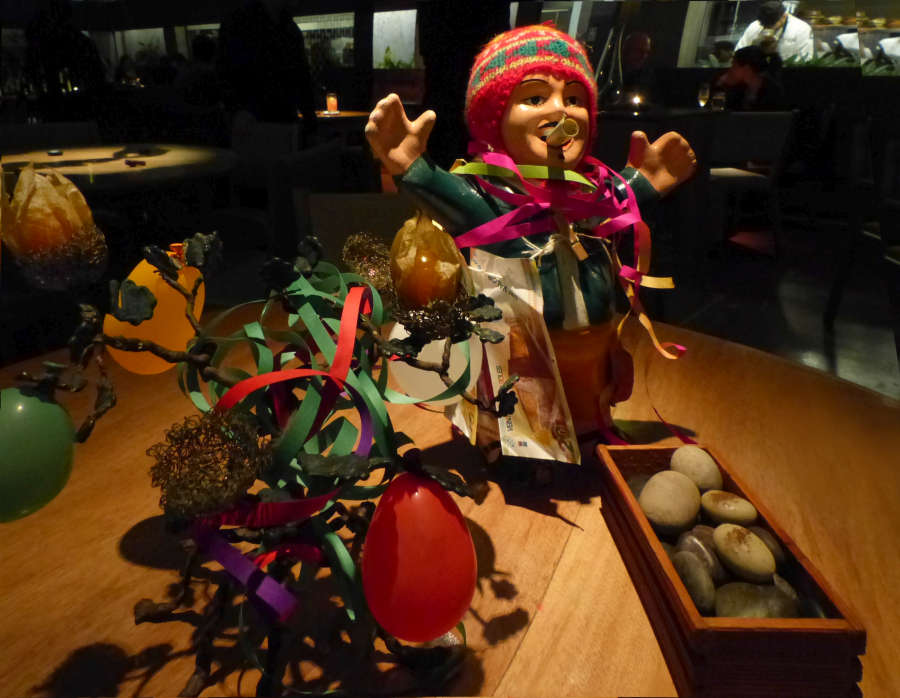 Restaurant bill was rolled up like a cigarette in the mouth of the god of prosperity. Elaborately presented mignardises were hidden in cape gooseberry husks and disguised as polished pebbles.