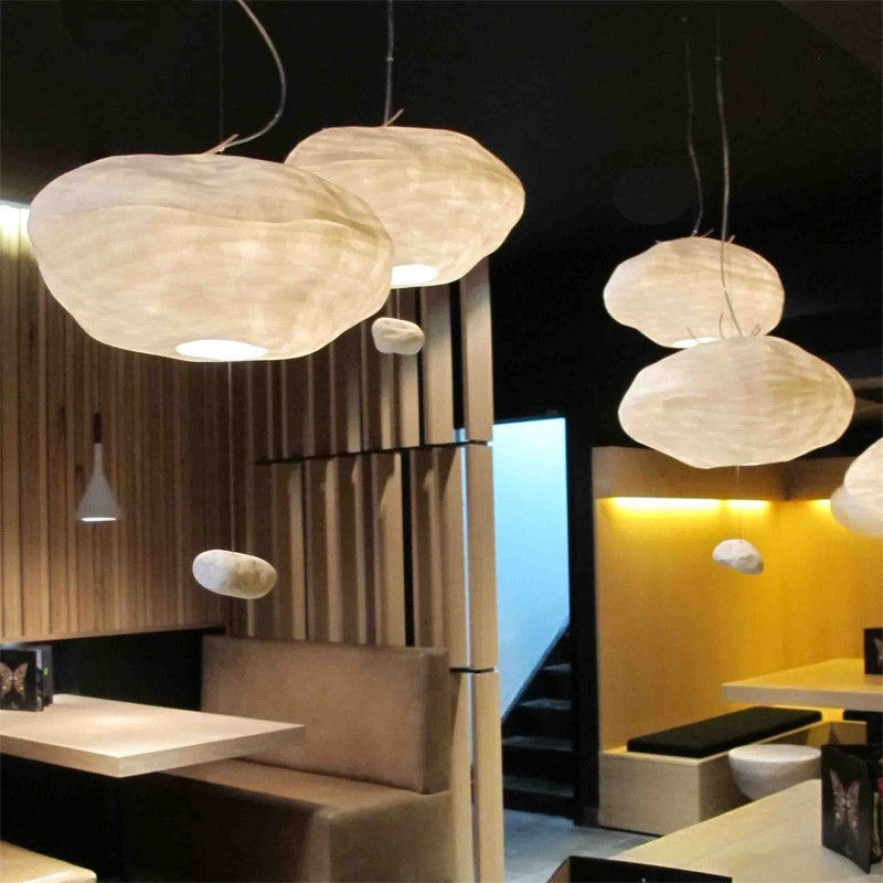 Cloud shaped pendant fixture of Japanese handmade paper with a rock at the bottom as counter balance